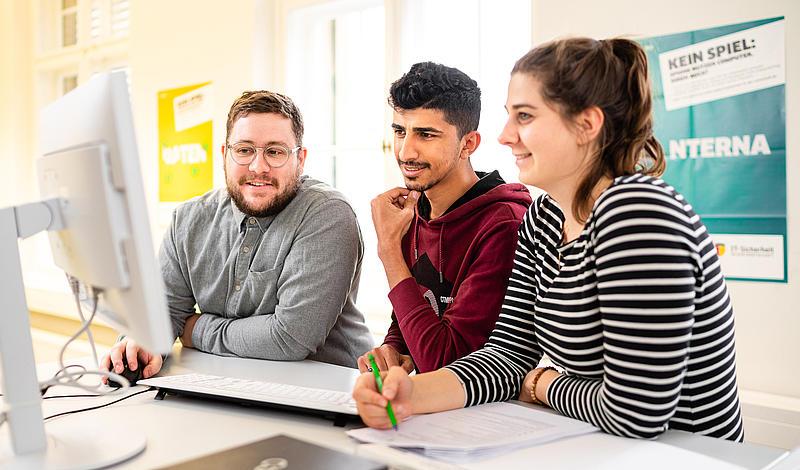Studierende schauen auf einen PC-Bildschirm.