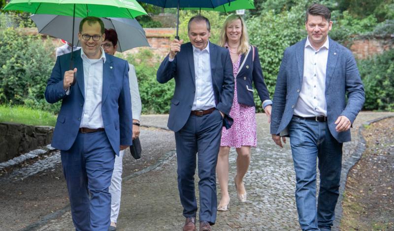 Rektor Alexander Kratzsch, Görlitz OB Octavian Ursu, Zittaus OB Thomas Zenker (vorn, von links nach rechts) sowie Kanzlerin Karin Hollstein und Prorektorin Sophia Keil. Das Wetter ist verregnet, der Fußweg ist naß. Außer OB Zenker tragen alle einen Schirm.